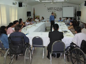 Participants sit around a table, a man stands in the centre.