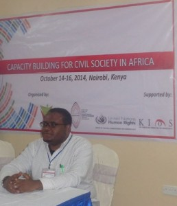 "Dagnachew Wakene sits in front of a banner that says ""Capacity Building for Civil Society in Africa"""