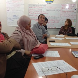 Training participants sit at table with charts behind them.