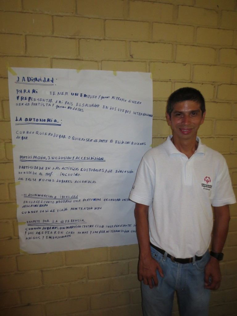 A workshop participant poses in front of a chart with the human rights principles written on it.