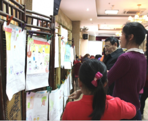 People view drawings by the girls with disabilities at the exhibition.