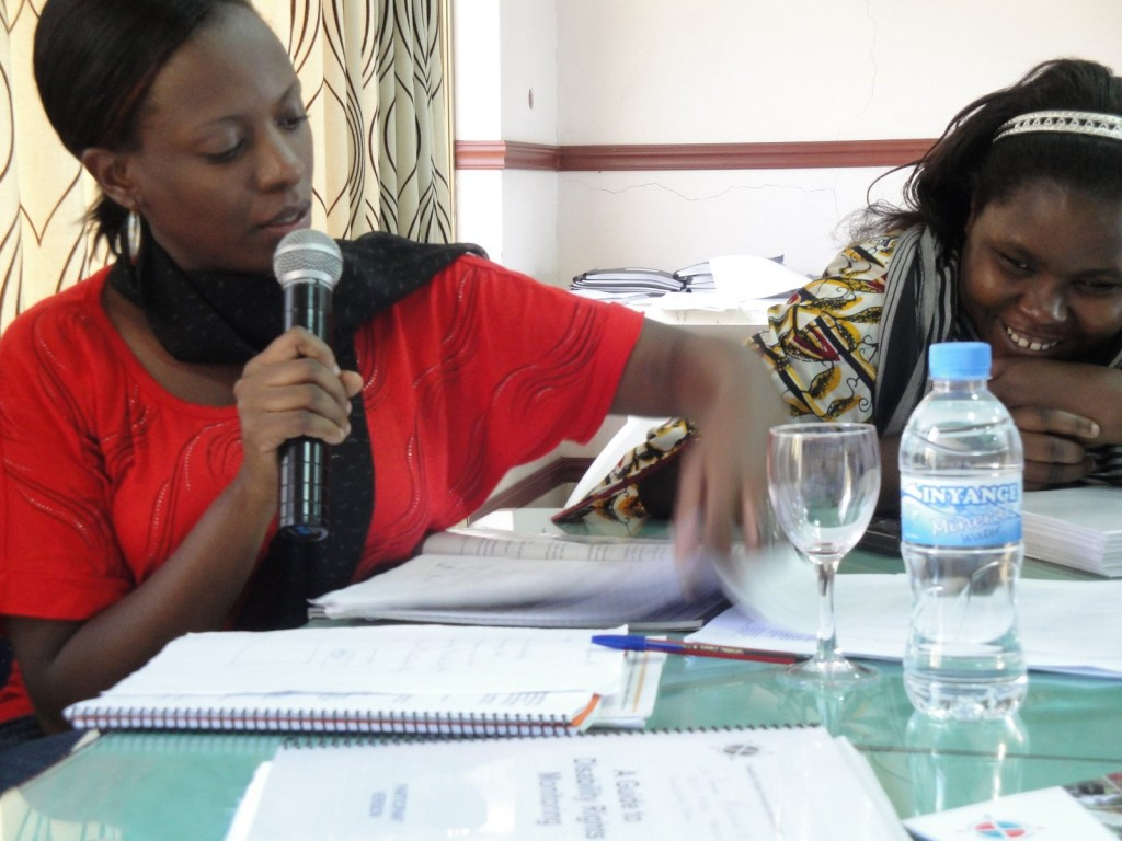 Gloria Namureme speaks into a microphone while looking at training materials. Esther Kyozira sits beside Gloria and smiles.